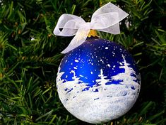 I start with a large 3-1/4 inch diameter blue glass ball ornament manufactured in the USA. I use acrylic paints and mediums to create the design.  This pattern is simple but oh, so pretty. The sparkly trees encircle the snow-spattered ball creating the effect of a snowy night in deep winter. My photography doesnt do this ball justice...it really sparkles! The active, dynamic quality of this scene makes it a great gift for any skier, snowboarder, or winter sports enthusiast.  A personalized…