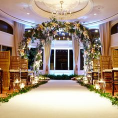 Brides: Glamorous Flower Arch. A dramatic flower-covered arch adorns the ceremony space. A mix of white-and-purple flowers, greenery, and hanging candles create an elegant and ethereal setting for this couple's celebration.