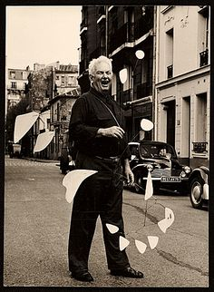 Citation: Alexander Calder holding his mobile on a Parisian street, 1954 / Agnès Varda, photographer.