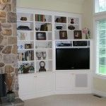Corner mounted TV with custom bookshelves.