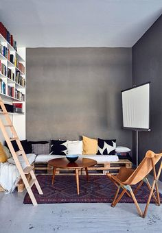 Home theater with home-build couch made from pallets.  The grey wall brings warmth to the room.