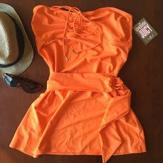 NWT juicy couture bathing suit coverup Tangerine colored coverup by Juicy Couture. Has an adjustable belt at the waist and the front ties at the bust and works as a halter. 80% nylon 20% spandex and lining is 76% polyester, 24% spandex. NWT Juicy Couture Swim Coverups