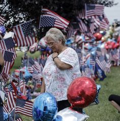 Angelica Delgadillo looks at a Lee Highway memorial for victims of the July, 16 shootings on Saturday, July 18, 2015, in Chattanooga, Tenn. U.S. Navy Petty Officer Randall Smith died Saturday from wounds sustained when gunman Mohammad Youssef Abdulazeez shot and killed four U.S. Marines and wounded two others and a Chattanooga police officer. Photo by Doug Strickland /Times Free Press