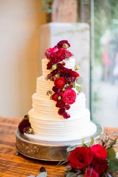 Ribbed white cake topped with vibrant red and pink flowers | Photo: Shelley Elena Photography | Florist: Bouquets of Austin | #bridesofaustin #wedding #weddinginspiration #cakes