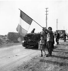 Ancien combattant de 1914-1918 et son petit-fils saluant avec le drapeau tricolore français, le passage des hommes du South Saskatchewan Regiment montés sur des Bren Carrier, chenillettes de transport britannique, à Fleury-sur-Orne. 20 juillet 1944. © Archives nationales du Canada