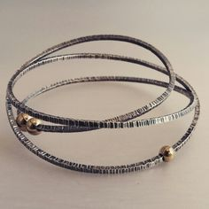 Textured and oxidised sterling silver orbit bangle with yellow gold balls. By Emily Becher