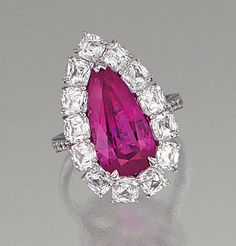 PINK SAPPHIRE AND DIAMOND RING.  The pear-shaped pink sapphire weighing 7.08 carats within a border of modified cushion-shaped stones, set between brilliant-cut diamond shoulders, mounted in platinum,  size 53.