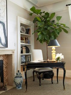 A small closet was converted to a bookcase, offering a more elegant storage solution. An antique writing desk and fiddle leaf fig tree complete this cozy nook.