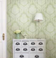 Welcome a luxurious greenery into your home with this fresh and expansive damask printed wall paper. A pale green backdrop embellished in crisp white brings a sharp finesse to your walls.