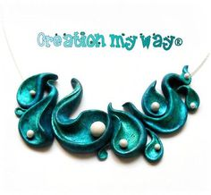 polymer clay sculptural necklace - swirly water stuff with pearls. Cool look.
