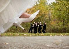 Giant bride foot stepping on groom and groomsmen. Haha I love this idea!