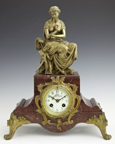Bronze Over Copper And Marble Mantel Clock, The Top With A Seated Cleopatra In Classical Dress Over A Clock With An Enamel Dial With Painted Floral Decoration, On A Shaped Base On Scrolled Feet   c.19th Century