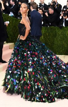 ZOE SALDANA  in a black Dolce & Gabbana gown with a multicolor feather train. Met  Gala 2016