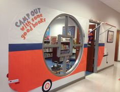 Camping Theme for school library: I made a pull-behind camper for the entrance to our camping-themed library. The awning is made from PVC pipe with fabric covering the top and suspended from ceiling with fishing line.