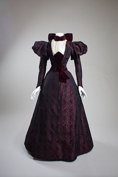 Dress, afternoon, c. 1897  Made by wearer  Silk brocade, velvet, chiffon    Gift of Dr. Leland S. Wellington, 1967  Worn by Ora Baily McCuthen   67.8.1ab    Ora Baily McCuthen, a concert pianist in San Diego, who designed and made her own clothes, wore this dress. She was the daughter of James O. Baily, one of the first men to discover gold in the Julian area and one of the founders of Banner, California.