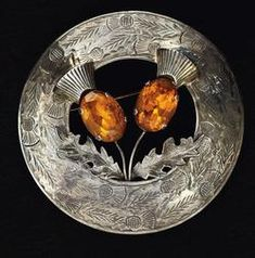 jewelry, Scotland, A Scottish brooch or kilt pin, Vintage, round silver engraved thistle brooch pin with two amber colored faceted stones.