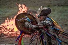 A shaman performs a ritual next to a fire in a remote part of the Siberian mountains. It's part of the festival 'Call of 13 Shamans' heldnear the village of Khorum-Dag in Tyva Republic, the geographic centre of the Asian continent