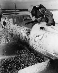 British soldier inspects a downed German fighter Bf.109E-1