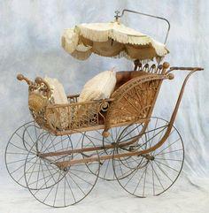 Victorian era baby pram with fringed parasol.