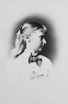 Princesa Alix de Hesse, depois Imperatriz Alexandra Feodorovna. Sua cabeça está virada para à direita de perfil. Ela veste um vestido de manga comprida decote alto e decorado com laços. Julho de 1878.