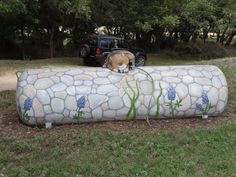 painted propane tank - cat sleeping on a stone wall