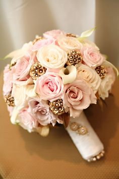 A unique touch added to a pink and white rose and mini calla bouquet: gold scabiosa pods with pearl accents. www.myfloweraffair.com can make this same bouquet.