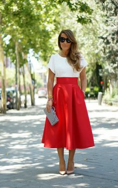 White t-shirt style blouse, high waisted red midi skirt, white heels, and black and white striped clutch