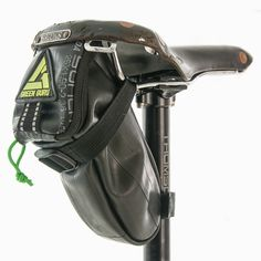 Shifter Saddle Bag. The Shifter upcycled inner tube saddle bag converts cycling's tube waste into an under seat bag designed to hold a tube, tool kit, and pump. Secured with a wrap around strap, this bag offers a stable storage solution for any bicycle.
