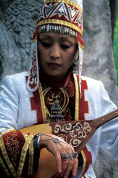Kazakh woman in traditional dress with traditional instrument, Kazakhstan