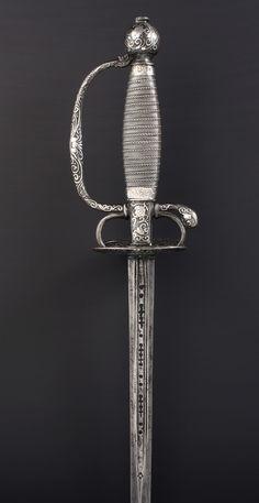 R-128AG.- Espada de ceñir. Francia, mediados siglo XVIII.Guarnición de hierro profusamente decorada con incrustaciones de plata. Puño de madera cubierto por una combinación de torzales de plata. Del mismo material son las virolas. Hoja recta, vaceo y calados en el primer cuarto, el resto a dos mesas levemente vaceadas. Long. Total: 90,5 cm; Long.Hoja : 74,5 cm; Anchura base hoja: 17 mm