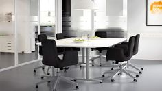 A meeting room furnished with black swivel chairs and a conference table in white/silver-colour