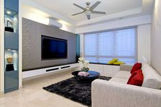 Wall Mount TV Living Room Design Ideas with white sofa and red cushion along black round coffee table on the black fur rug and cream floor plus white ceiling fan