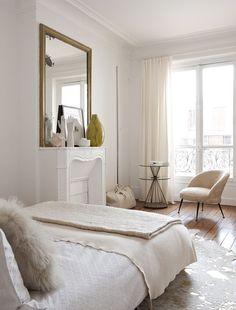 chambre parisienne, parquet, moulures, cheminée et miroir ancien à cadre doré, rideaux et textiles clairs