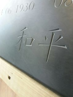V cut Chinese letters in Welsh slate By Dan Anderson