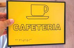 Cafetería. Placa de señalización con texto en Braille. Accesibilidad.