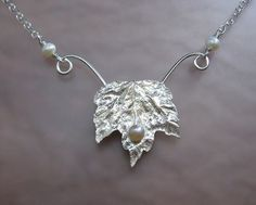 Maple leaf necklace fashioned from a real maple leaf fossilized in sterling silver, that holds a 5mm round luminous white freshwater pearl  http://www.kryziakreationsstudio.com/products/maple-leaf-necklace-with-pearls-in-sterling-silver  $175.00