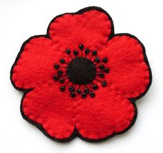 Red Handstitched felt and bead Poppy from Bugs and Fishes by Lupin. Simple design, but very effective. These are for sale at her website.
