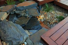 A hand made natural stone waterfall cascades under Merbau decking to a pebble fish pond.  The strategically placed outdoor lighting accentuates the water flow at night.  Full Bentleigh project can be seen at Intrinsic Landscapes website.