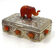 "An antique sterling gold washed table box with hand chased floral work and applied carnelian hardstone elephants on the sides of the box and a larger elephant finial on the hinged lid. 5 3/4"" by 3 1/2"" by3 1/2"" tall to the finial. The box is 1 3/4"" deep. The interior is ebony wood lined. Manufactured by the Bensabott Company of Chicago."