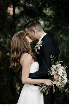 A beautiful two piece strapless wedding dress with loose hair and elegant jewellery and groom in a black suit - bouquet with soft pink and green touches