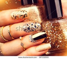 Golden Nail art manicure. Holiday style bright Manicure with gems and sparkles. Bottle of  Nail Polish. Fashion rings with diamonds, Trendy Accessories. Beauty hands. Stylish Nails, Nailpolish - stock photo