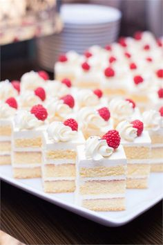 A cut up and ready to serve wedding cake, decorated with fresh raspberries.