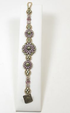 A charming bracelet in a floral design beaded with Czech glass beads. The floral motifs consist of luster opaque amethyst Super Duos
