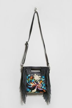 A genuine leather bag by Raj L.A.™ featuring a bird and floral embroidery, a hidden magnetic-snap closure, a handle cutout, interior slip pocket, fringed side trim, and an adjustable crossbody strap.