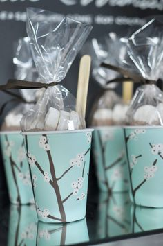 "winter party cocoa cups: ""8oz. paper cups were dressed up with a simple paper wrap, filled with hot cocoa powder, marshmallows and adorned with a wooden spoon! Serve with hot water and encourage guests to warm up and take a cup home!""  {Twig & Thistle}"