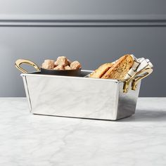 Shop Bates Stainless Steel Basket. Rectangular server brings bread, napkins, flatware, etc. to the table. Handmade in a traditional silhouette with a modern twist––a mix of metallics. Pair with our Bates stainless steel serving tray.