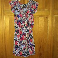 Two Piece Junior Dress Beautiful floral. Crape dress with a black tank slip.  Like new.  Elastic waist.  Ruffle capped sleeves. Ruffle v neck with two button closure. Full Tilt Dresses