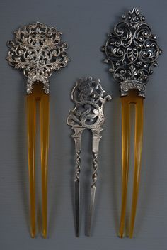 THREE PIERCED STERLING SILVER HAIRPINS, c. 1900 Two amber celluloid with scrolling filigree silver tops. One all silver with twisted prongs and meandering foliage design.