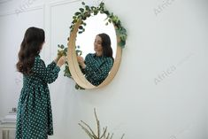 Woman decorating mirror with eucalyptus branches at home. Space for text. Buy Creativity & Imagination. Take a look at what the world's best photographers have to offer at africa-images.com Eucalyptus Branches, Best Photographers, Photo Library, Hanging Chair, Imagination, Creativity, Africa, Stock Photos, Decorating