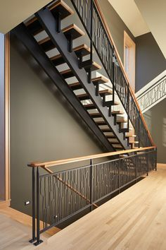 These striking steel and wood stairs have water jet-cut steel railings with a pattern based on hand-drawn ink brush strokes.